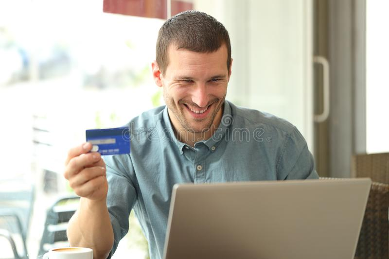 Happy adult man buying online with credit card and laptop stock photos