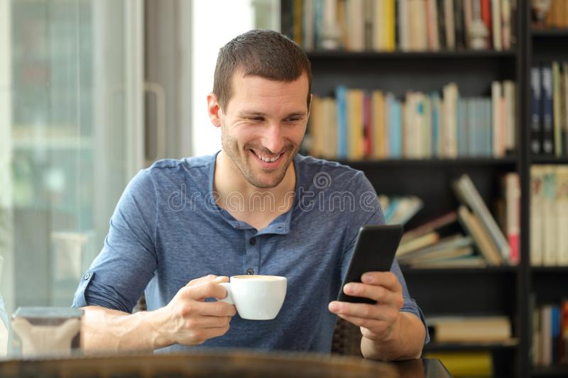 Happy adult man checking smart phone in a coffee shop. Happy adult man checking smart phone holding a cup sitting in a coffee shop royalty free stock image