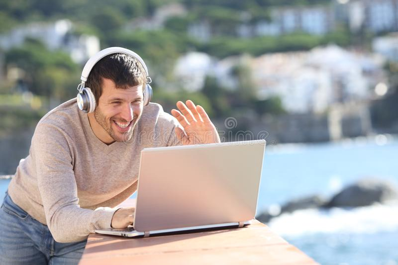 Happy adult man having a video call with a laptop stock photos