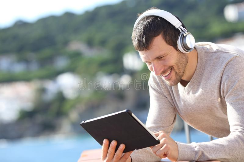 Happy adult man with headphones checking tablet content stock photography