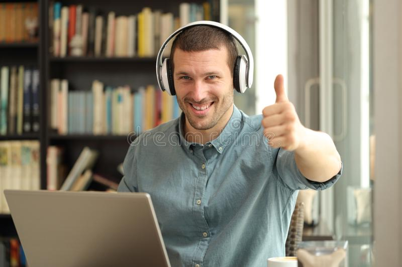 Happy adult man with laptop and headphones with thumbs up. Happy adult man with laptop and headphones gesturing thumbs up sitting in a coffee shop royalty free stock photo