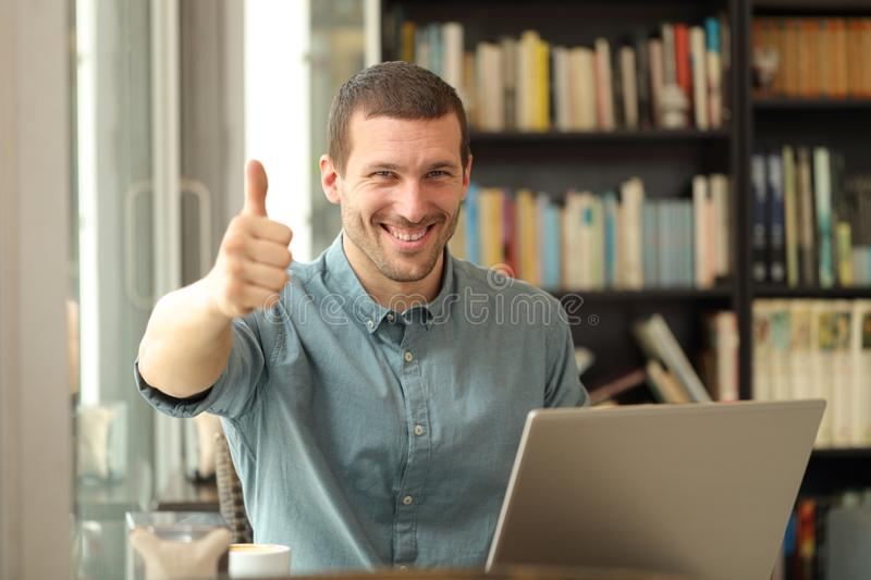 Happy adult man with laptop with thumbs up stock photography