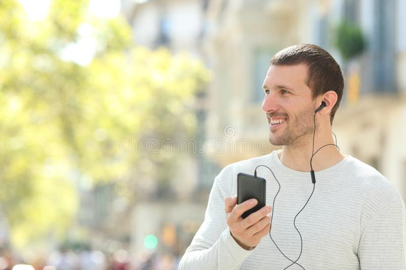 Happy adult man listening to music looking at side in the street. Happy adult man listening to music with earphones and phone looking at side in the street stock photo