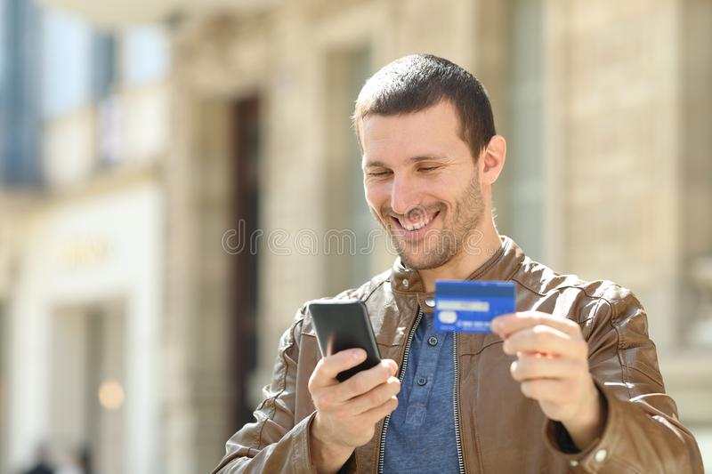 Happy adult man paying with credit card and phone in the street. Happy adult fashion man paying with credit card and mobile phone standing in the street stock photography