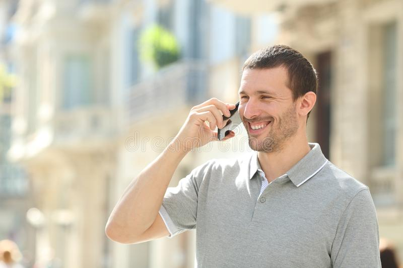 Happy adult man talking on phone in the street. Happy adult man talking on mobile phone walking in the street stock photos
