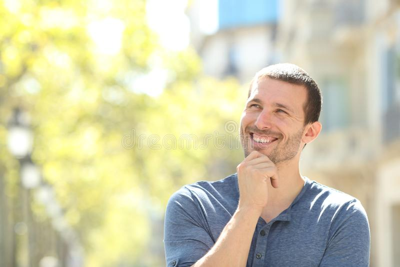 Happy adult man thinking looking at side in the street. Front view portrait of a happy adult man thinking looking at side standing in the street stock photo