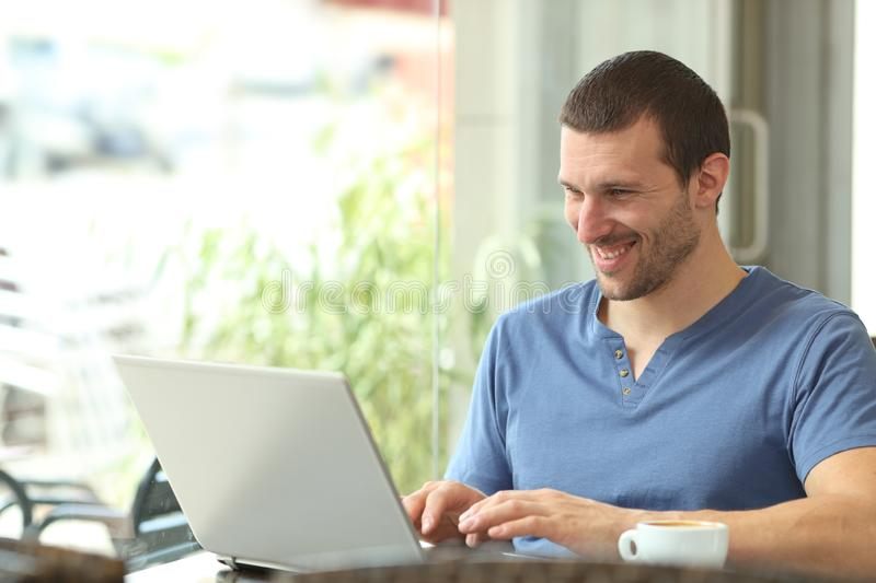 Happy adult man using a laptop in a bar. Happy adult man using a laptop writing content sitting in a coffee shop stock images