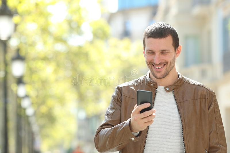 Happy adult man using a smart phone in the street. Front view portrait of a happy adult man using a smart phone walking in the street stock photography