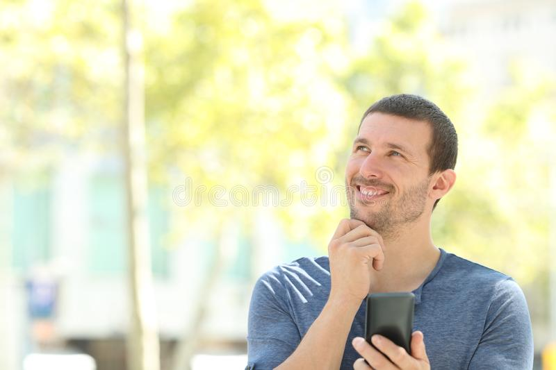 Happy adult pensive man holding phone looks at side royalty free stock image