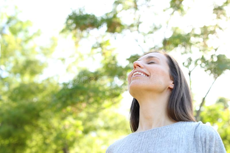 Happy adult woman breathing fresh air in a forest stock image