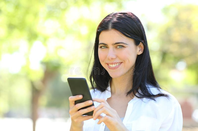 Happy adult woman holding phone looking at camera royalty free stock photo
