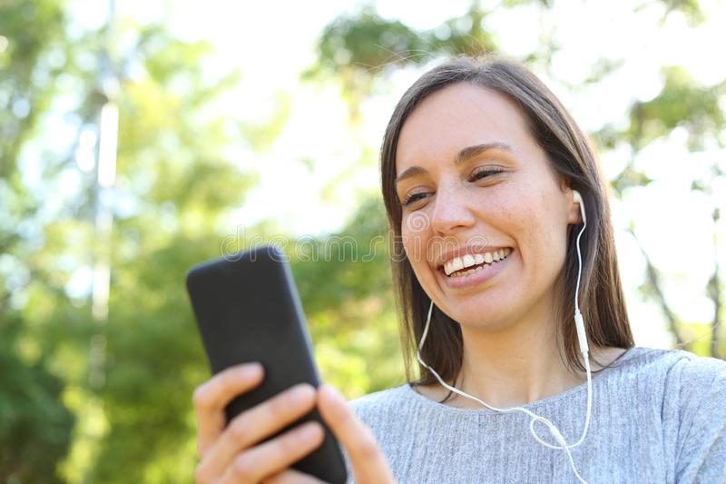 Happy adult woman listening to music checking phone in a park royalty free stock photos