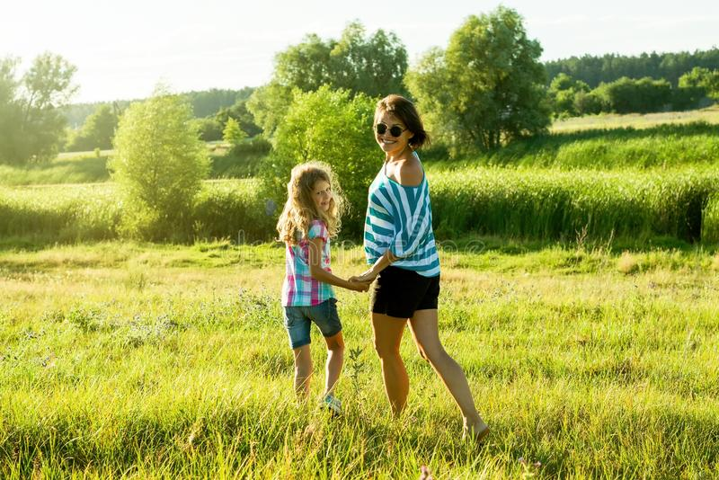 Happy adult woman playing outdoors with her daughter child girl. Happy adult women playing outdoors with her daughter child girl. Outdoor summer portrait royalty free stock photography