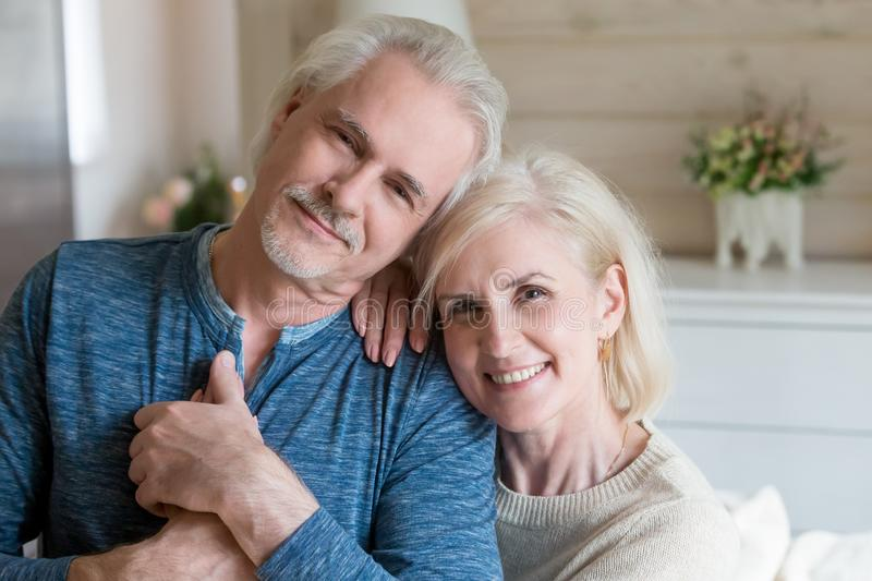 Happy affectionate mature man and woman embracing looking at cam royalty free stock images