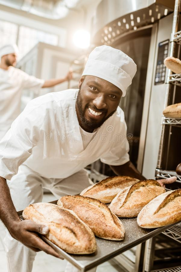 Happy african american baker taking bread loaves from oven. At baking manufacture stock image