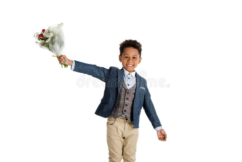 happy african american boy standing with bouquet stock image