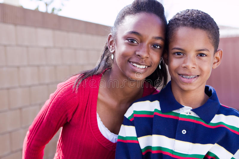 Happy African American brother and sister smiling. stock photos