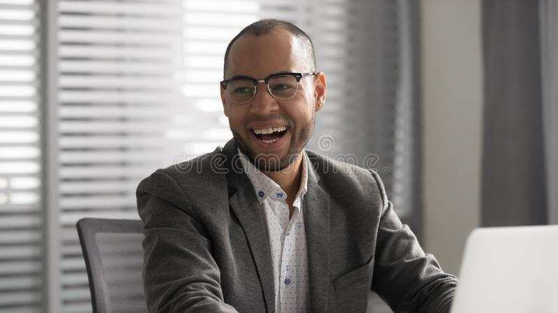 Positive african businessman in suit laughing sitting at work desk royalty free stock photos