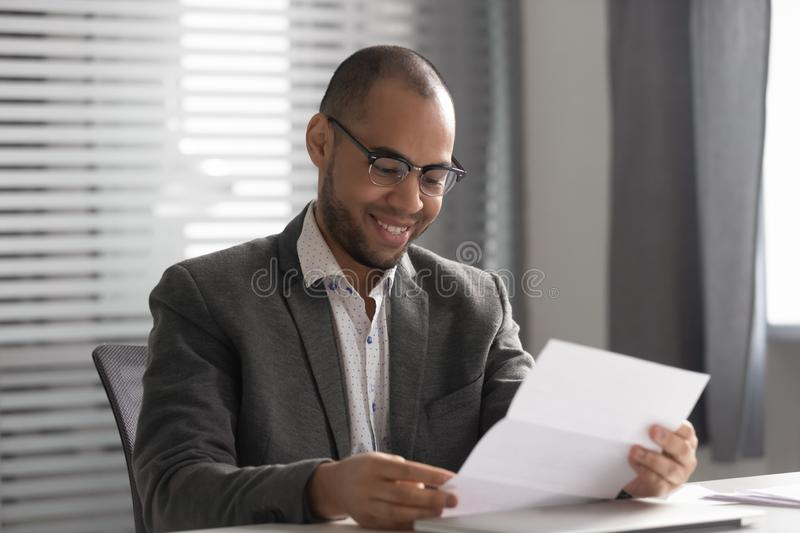 Happy African American businessman reading document, receiving good news royalty free stock photography