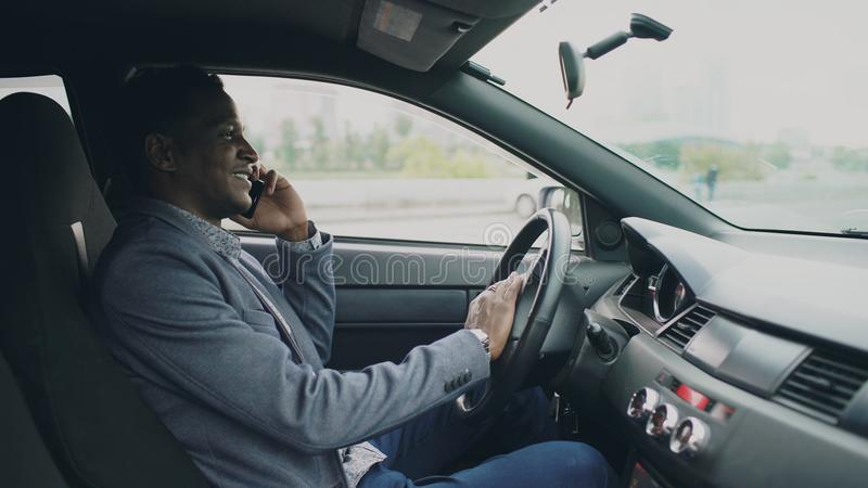 Happy mixed race businessman talking phone while sitting inside his car outdoors royalty free stock image