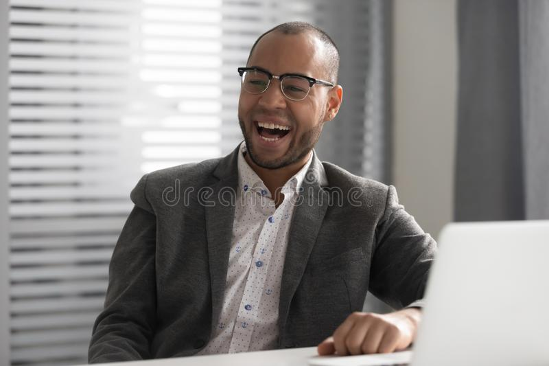 Happy African American businessman laughing at funny joke during break royalty free stock photos