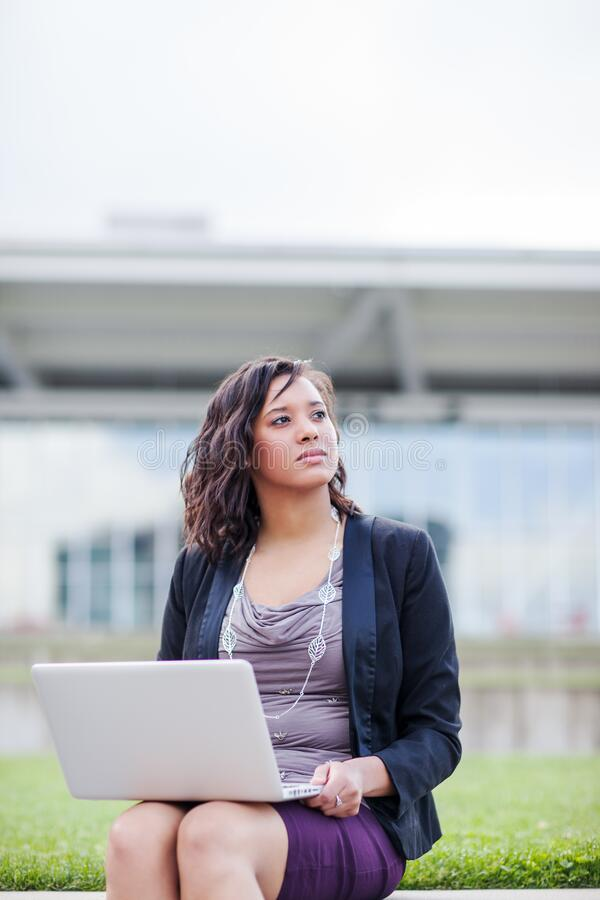 Happy African American businesswoman working on her laptop stock photography