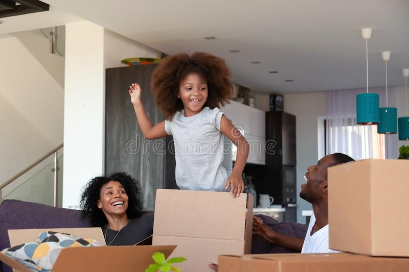 Happy African American child and parents unpacking boxes in new house stock images