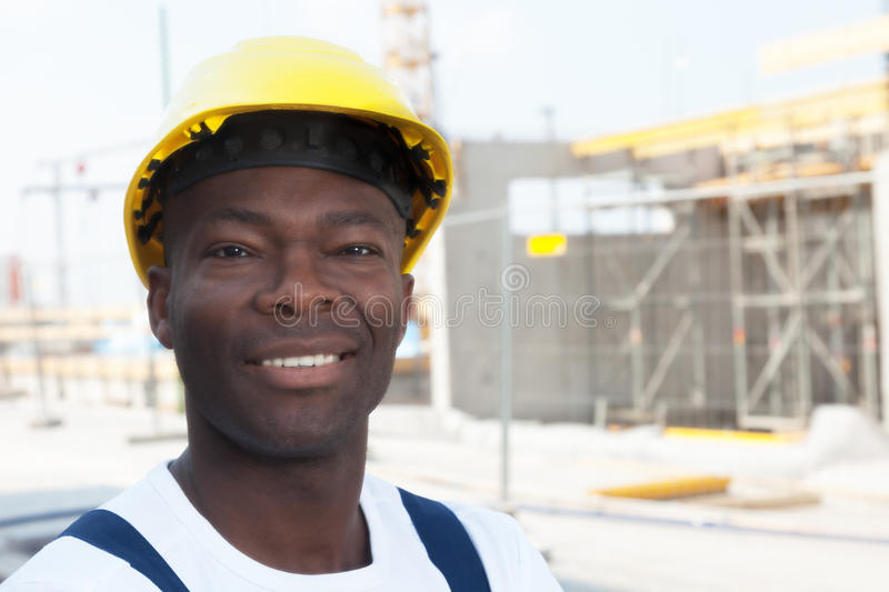 Happy african american construction worker at building site. With working area in the background royalty free stock image