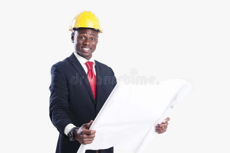 Happy african american construction worker holding blueprint.  royalty free stock photography