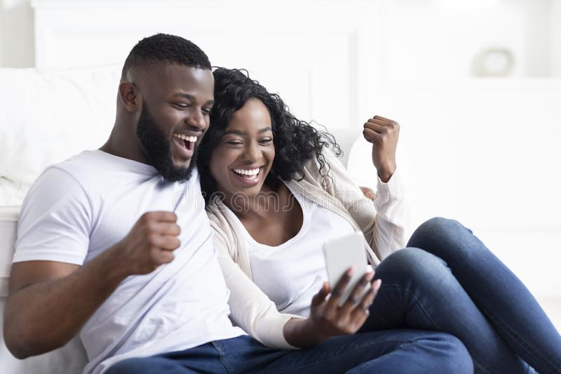 Happy millennial couple celebrating win with smartphone, shouting at home stock images