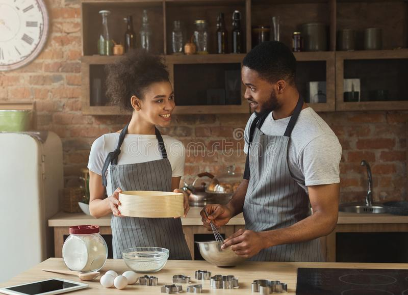Happy african-american couple cooking cookies together. Family preparing pastry stock image