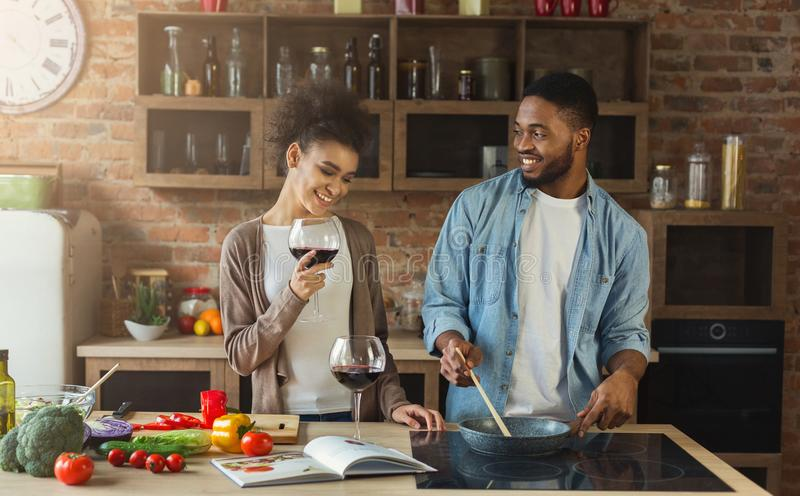 African-american couple cooking dinner and drinking red wine. Happy african-american couple cooking dinner together and drinking red wine stock photography