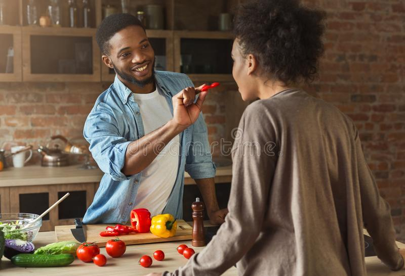 Happy african-american couple cooking in loft kitchen. Happy african-american family at kitchen. Black couple cooking in loft interior royalty free stock photography