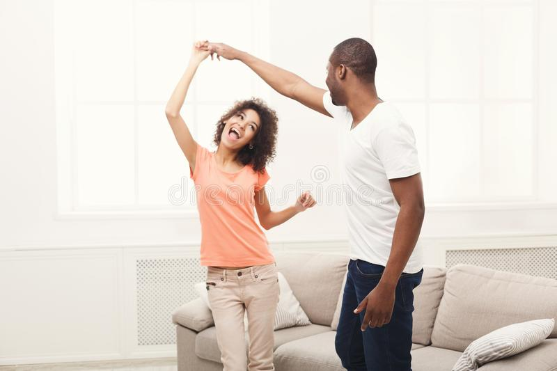 Young happy black couple dancing at home, copy space stock photos