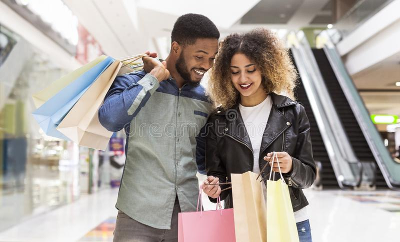 Happy african american couple discussing purchases and smiling stock photo