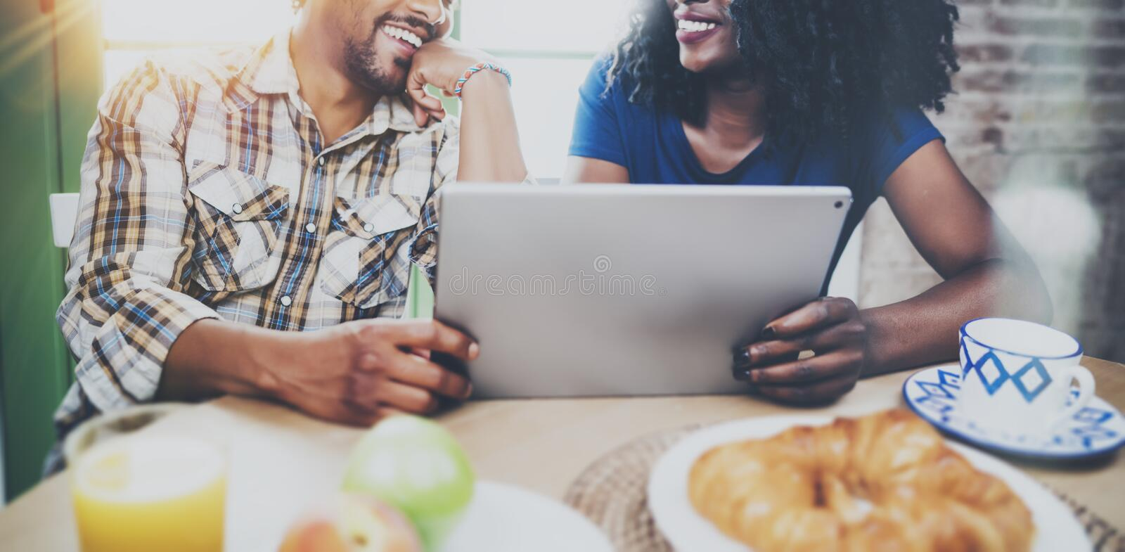 Happy african american couple are having breakfast together in the morning at the wooden table.Smiling black man and his. Happy african american couple are stock photography
