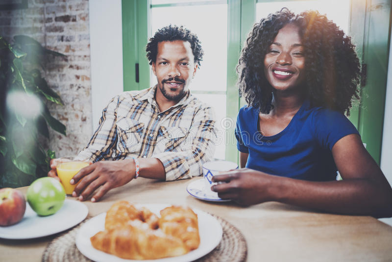 Happy african american couple are having breakfast together in the morning at the wooden table.Smiling black man and his stock image