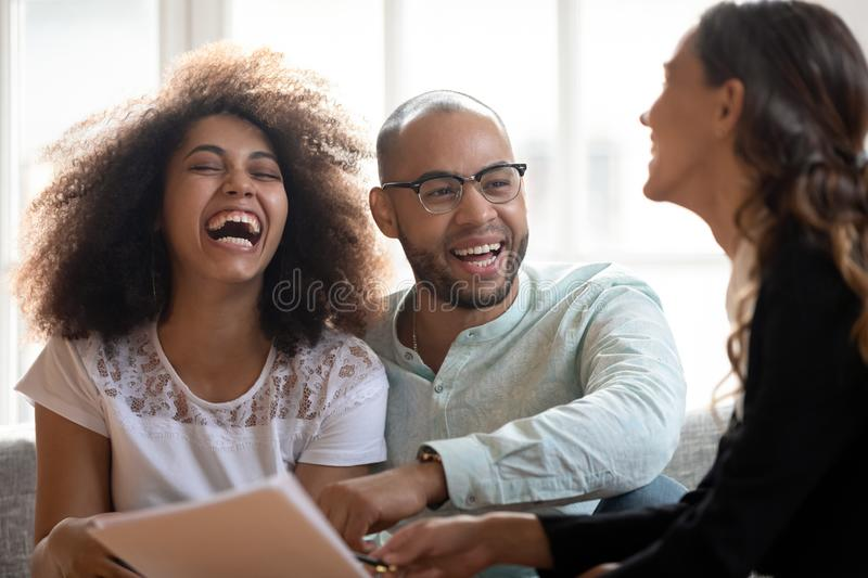 Happy African American couple laughing at meeting with realtor stock photo
