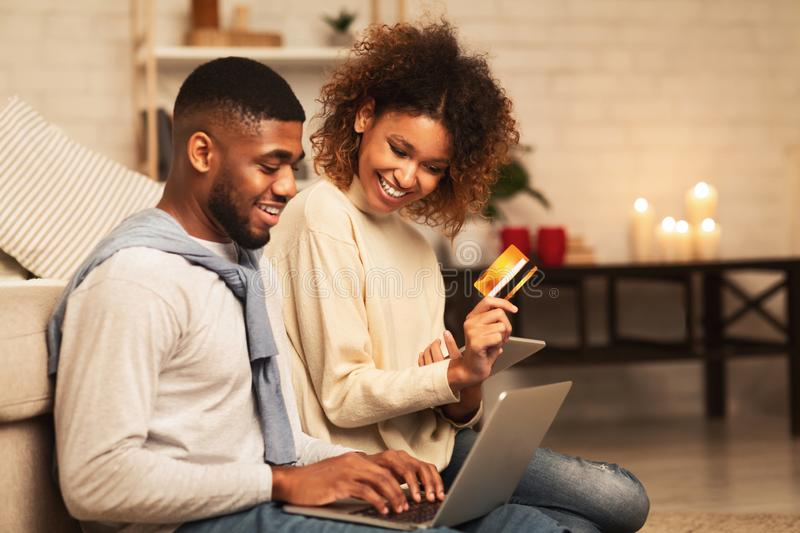 Happy african-american couple looking at laptop and buying online stock photography
