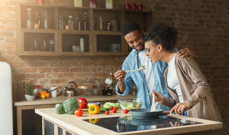 Happy african-american couple preparing dinner. In loft kitchen at home. Family cooking healthy food royalty free stock photography