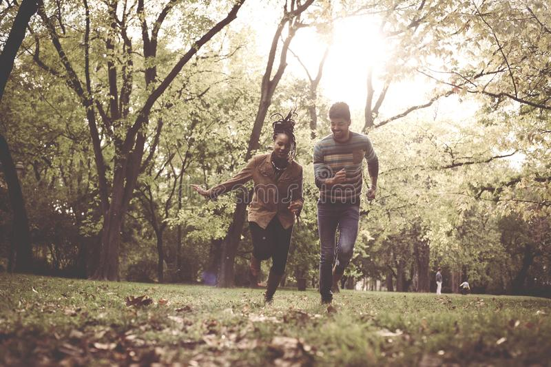 Happy African American couple running and catching in park. royalty free stock images