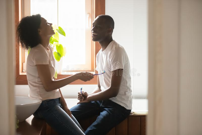Happy biracial couple talk cleaning teeth in morning stock images