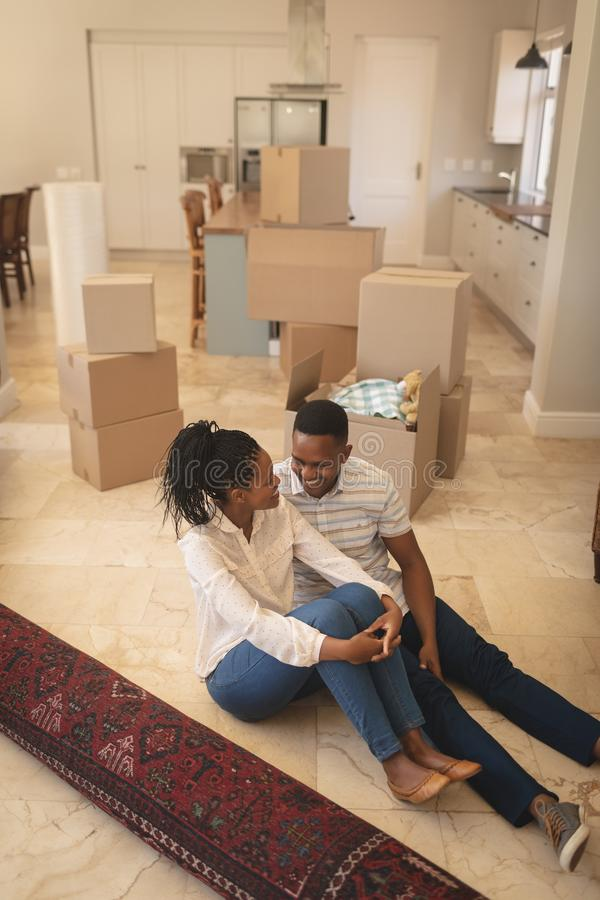 Happy African American couple sitting on floor and talking with each other stock photography