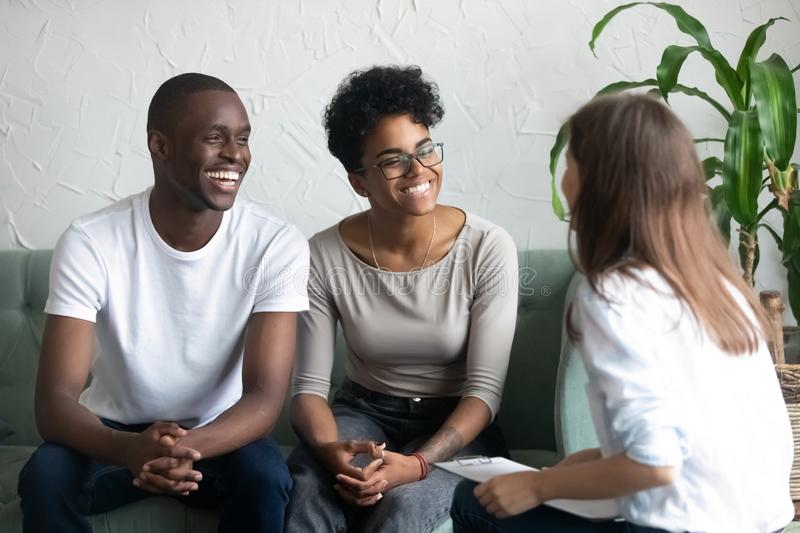 Happy African American couple at successful visit psychologist. Smiling wife and husband sitting together on couch after good family therapy session, satisfied stock photos