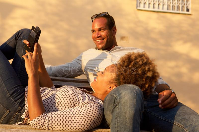 Happy african american couple together on park bench stock photos