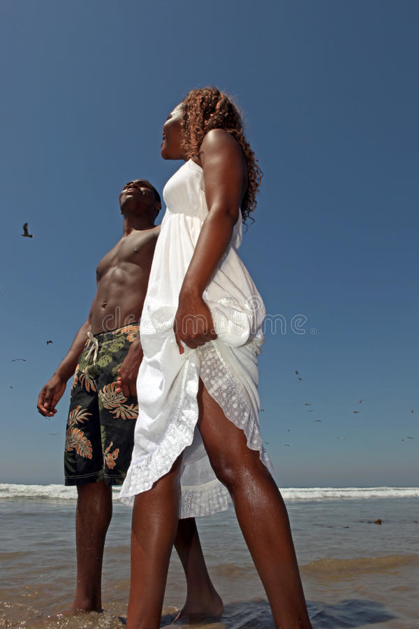 Happy African American Couple Walking Along the Be stock photo