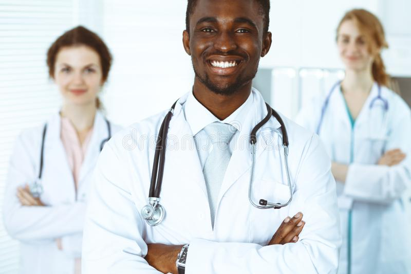 Happy african american doctor with medical staff at the hospital. Multi ethnic people group royalty free stock photography