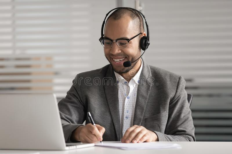 Happy African American employee in headset making notes, using laptop royalty free stock photos