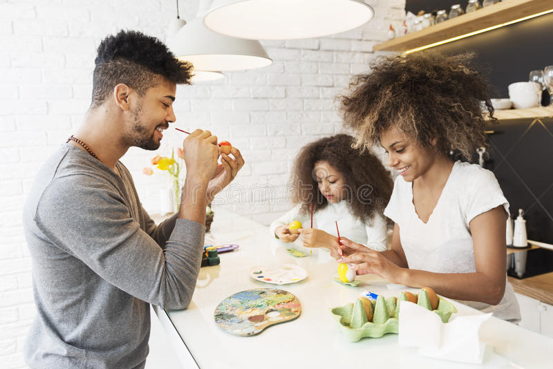 Happy African American family coloring Easter eggs stock images