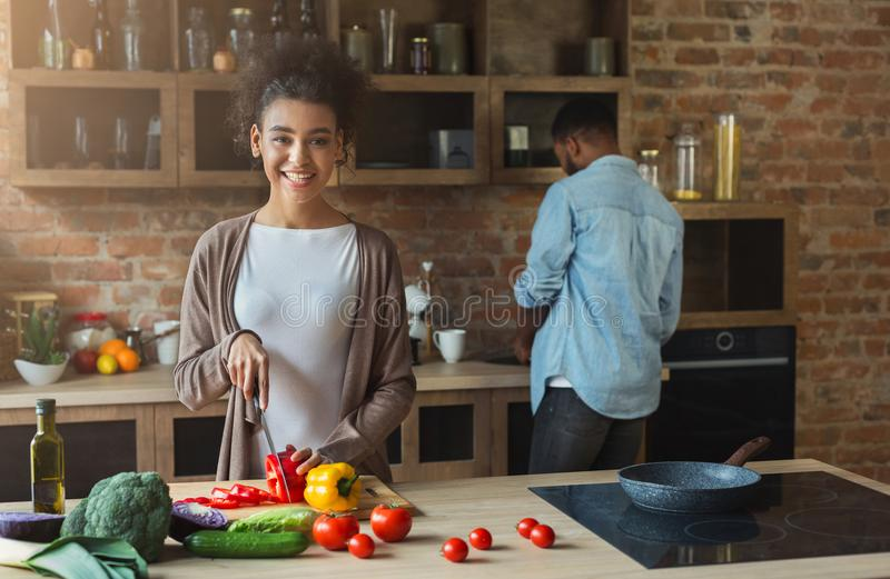 Happy african-american family cooking in loft kitchen. Happy african-american family at kitchen. Black couple cooking in loft interior royalty free stock images